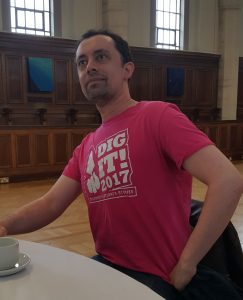 Dark haired man in pink T shirt with the words Dig It! on